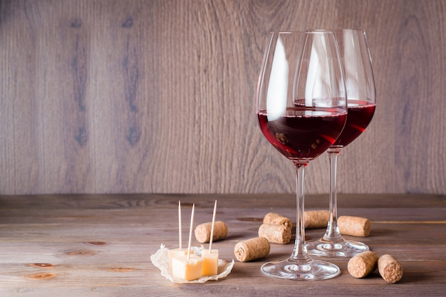 Two glasses with red wine, pieces of cheese and cork on a wooden table