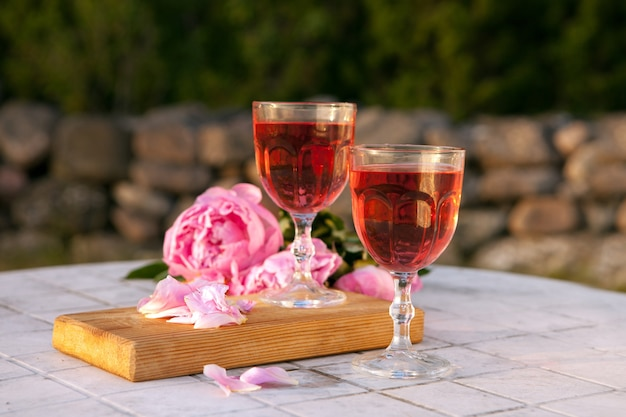 Two glasses with rose wine and pink peony bouquet. delicious refreshing drink, huge blossoming flowers at the table at sunset