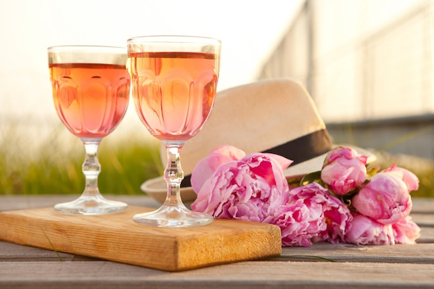 Two glasses with rose wine and pink peony bouquet refreshing drink blossoming flowers and mens hat