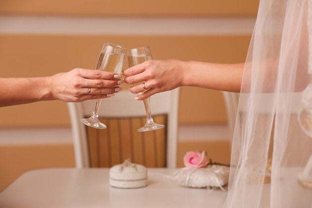Two glasses with sparkling champagne in hands, holiday concept, wedding