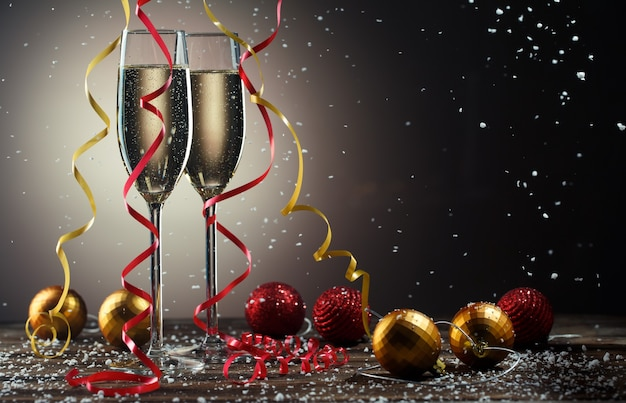 Two glasses with sparkling champagne, snowflakes and christmas red and yellow ball with ribbons.