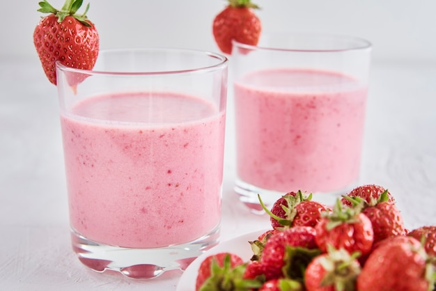Two glasses with strawberry shake and fresh berries