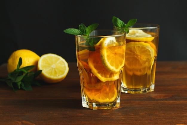 나무 소박한 배경에 유리에 레몬과 민트 잎을 곁들인 전통 아이스티를 곁들인 두 잔...