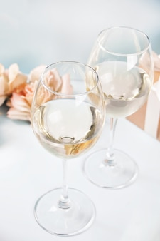 Two glasses with white grape wine with roses and gift box on the background. romantic dinner concept.