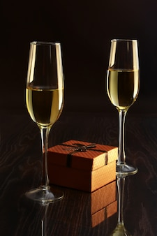 Two glasses with white wine and gift box on mirror table. celebrities composition.