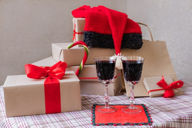 Two glasses with wine stand near shopping bag and gifts on the festive table at home.