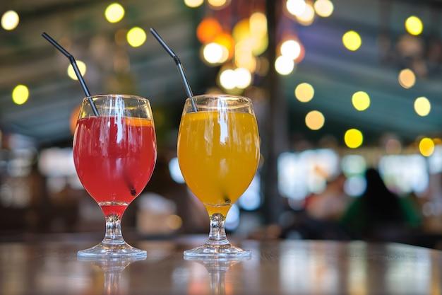 Два стакана с желтым и красным вкусным сладким напитком на столе в ресторане.