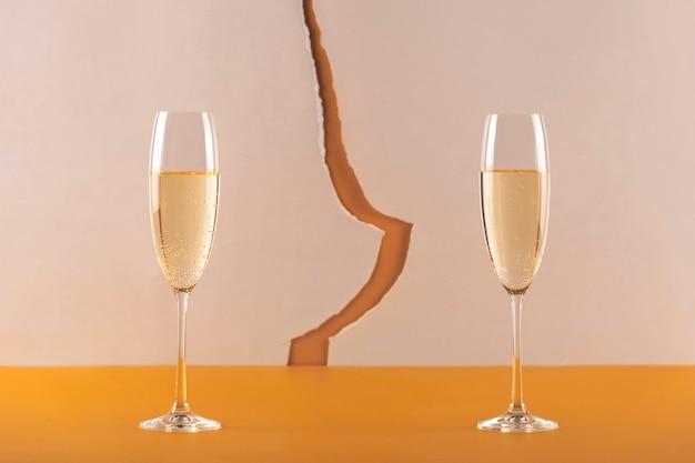 Два бокала шампанского на фоне трещины. раздельное рождественское понятие во время пандемии