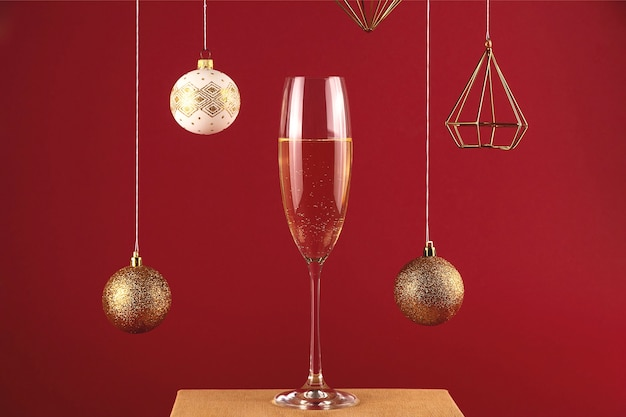 크리스마스 공 및 장식 빨간색 배경에 스탠드에 샴페인 두 잔. 휴일 및 새 해 개념.
