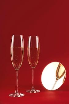 Два бокала шампанского с отражением в маленьком круглом зеркале на красном