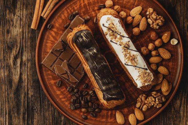 Два глазированных эклера, украшенные орехами и кофейными зернами