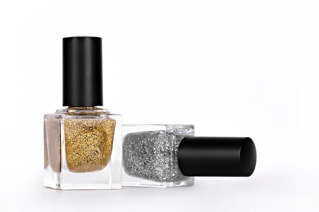Два блестящих лака для ногтей золотого и серебряного цвета на светлом фоне