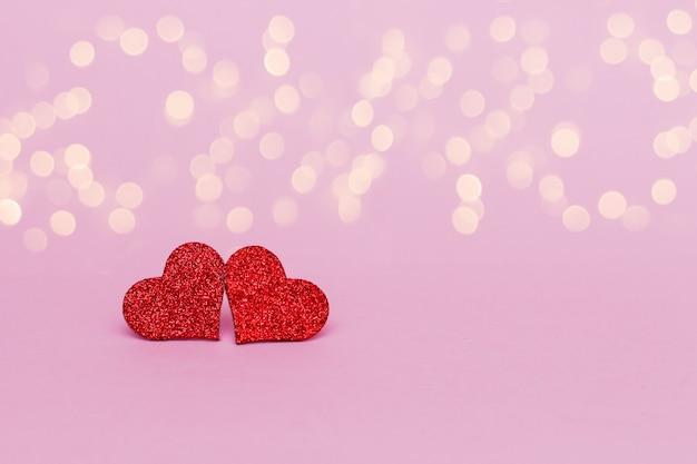 ピンクの背景に2つのキラキラ輝く赤いハート。スペースをコピーします。バレンタインデーの背景