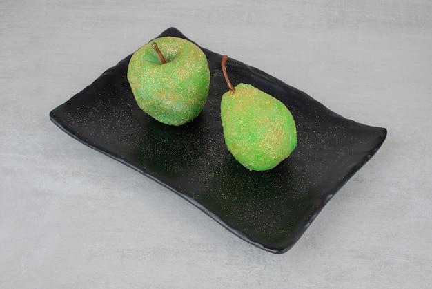 白い表面の黒いプレートに2つのキラキラ光るリンゴ。