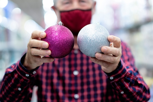 Two glittery christmas balls, silver and purple, in the hands of an old man wearing a medical mask due to coronavirus infection