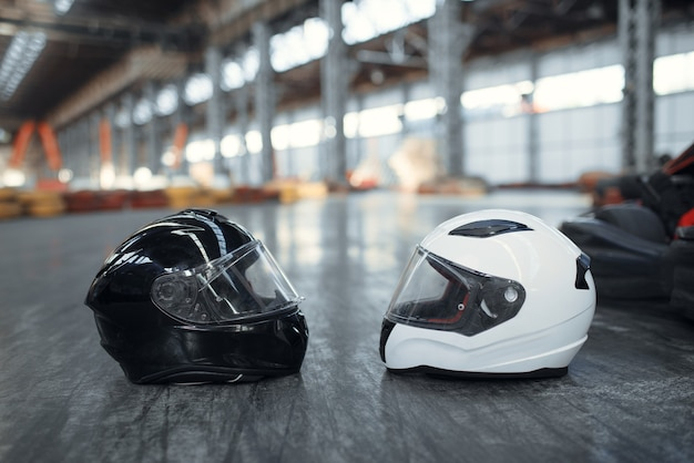 Two go kart helmets on the ground, karting auto sport concept.