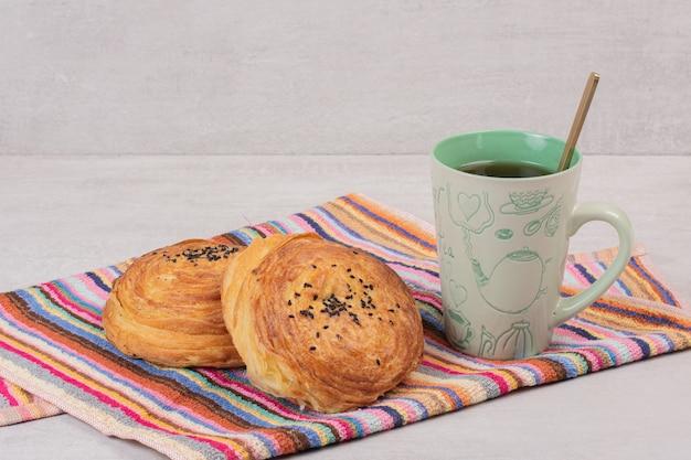 Due gogals e una tazza di tè sulla tovaglia.