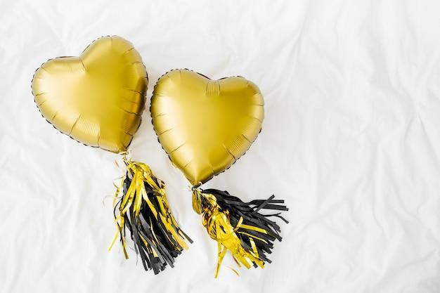 Два золотых шара в форме сердца на белой кровати. концепция любви. праздник. день святого валентина или украшение дня рождения / девичника. металлический шар
