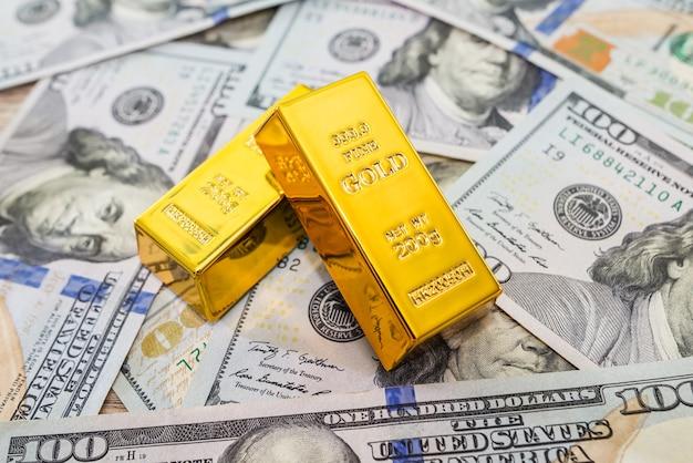 Два золотых слитка на банкноте долларов сша в качестве фона