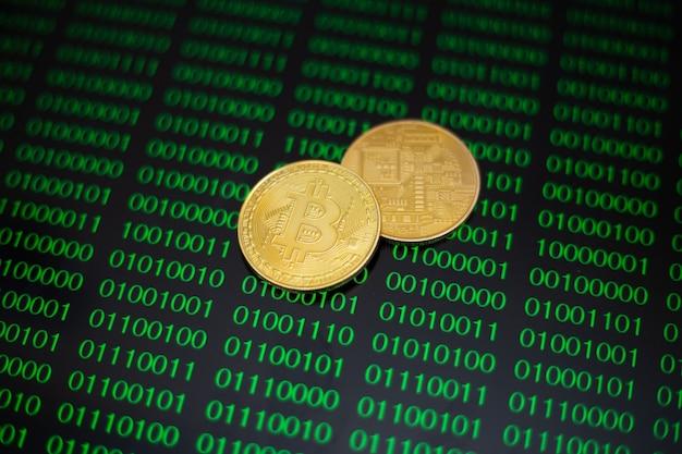 Два золотых биткойна на фоне зеленых нулей и единиц программного кода