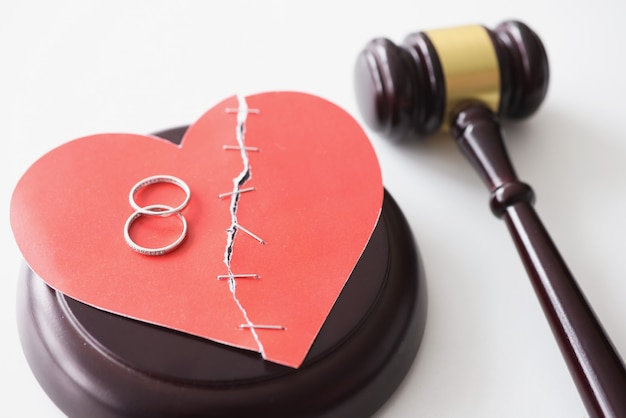 Two gold rings lying on red paper heart near judge hammer closeup
