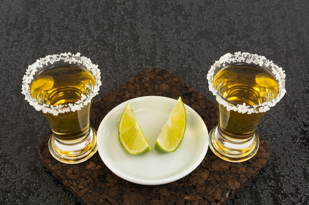 Two gold tequila shots with lime