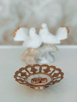 질감 있는 반짝이 접시에 사랑과 로맨스를 상징하는 두 개의 금색 웨딩 밴드