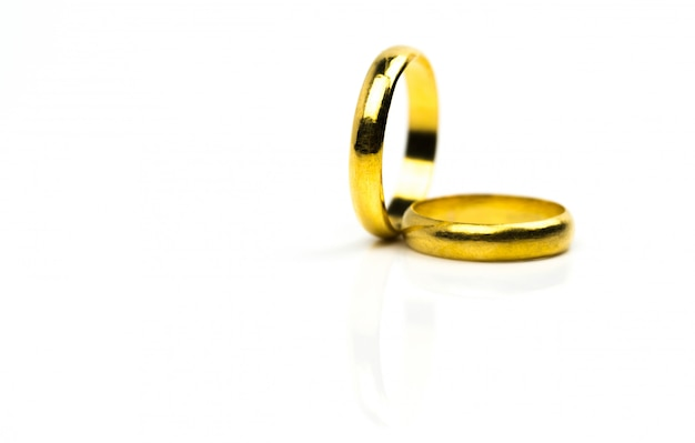 コピースペースを白で隔離される2つの金の結婚指輪
