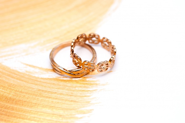 Two gold wedding rings on an abstract gilded acrylic
