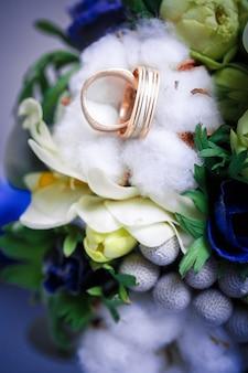 Два золотых обручальных кольца и красивый бело-голубой букет