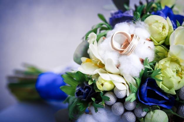 2つの金の結婚指輪と美しい青と白の花束