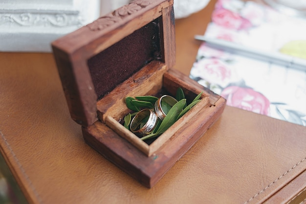 Two gold wedding rings in a beautiful wooden casket with green moss