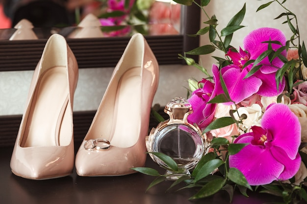 Two gold wedding rings, bouquet, bride shoes and other wedding accessories