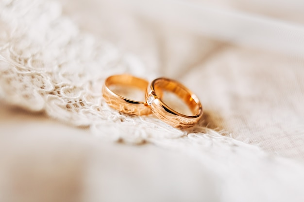 Two gold wedding rings for the bride and groom with a gem on white lace