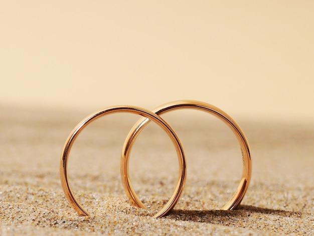 Два золотых обручальных кольца на песке, медовый месяц.