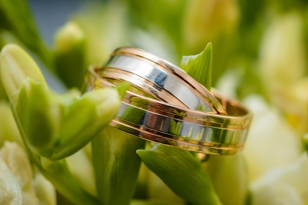 Two gold wedding rings lie on the flowers of a beautiful bouquet