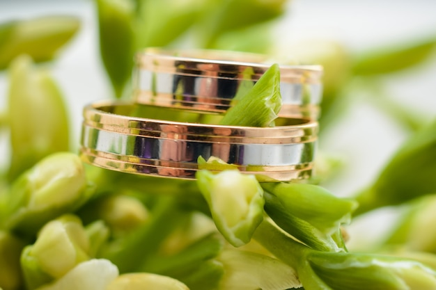 Two gold wedding rings lie on the flowers of a bouquet
