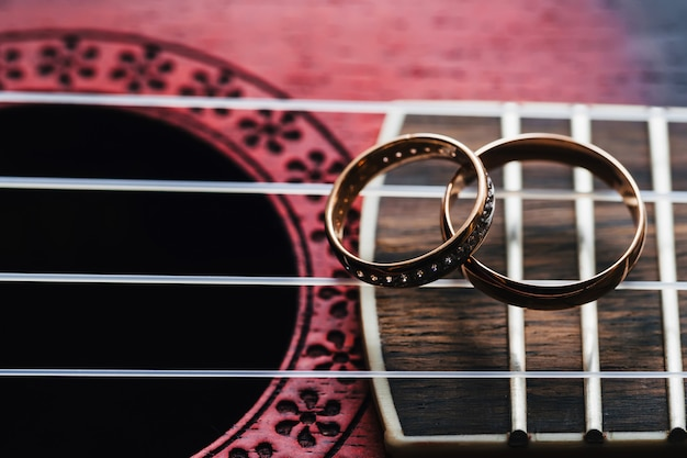 Two gold wedding rings lie on guitar strings