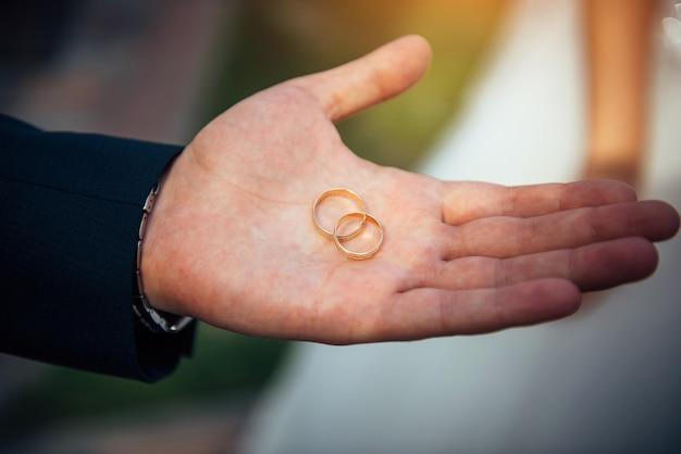 2つの金の結婚指輪は、男性の開いた手のひらにクローズアップで横たわっています。伸ばした手で結婚指輪を持っている若い新郎