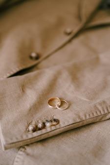 버튼이있는 베이지 남성용 블레이저에 두 개의 골드 결혼 반지