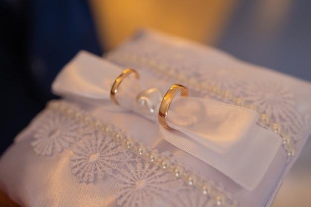 枕に2つの金の結婚指輪。