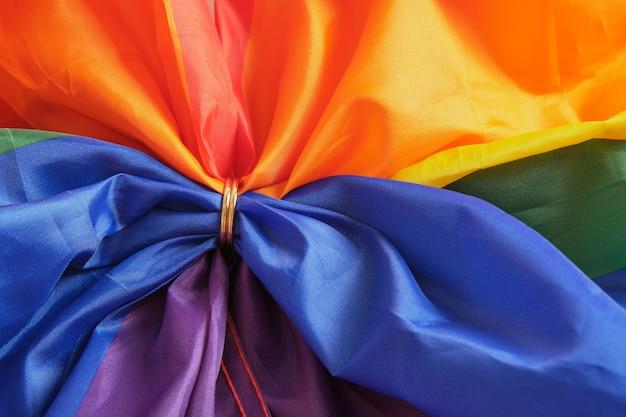 무지개 lgb 플래그에 두 개의 금 결혼 반지입니다. 동성애 결혼. lgbt 권리 개념 복사 공간