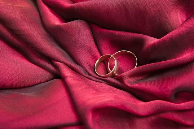 Два золотых обручальных кольца на красной ткани