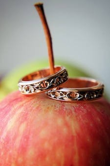 Two gold wedding rings on red apple, close-up. vintage rings for bride and groom, selective focus. concept of the wedding
