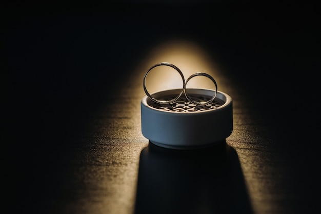 Two gold wedding rings in a white box on a black background