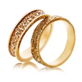 Два золотых обручальных кольца с абстрактной поверхностью, изолированные на белом фоне