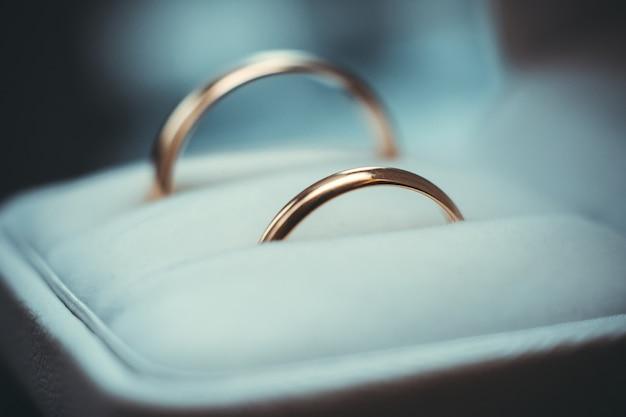Два золотых обручальных традиционных кольца лежат в белой коробке