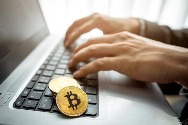 노트북을 사용하는 사업가 손으로 키보드에 두 개의 황금 bitcoins 동전을 닫습니다.