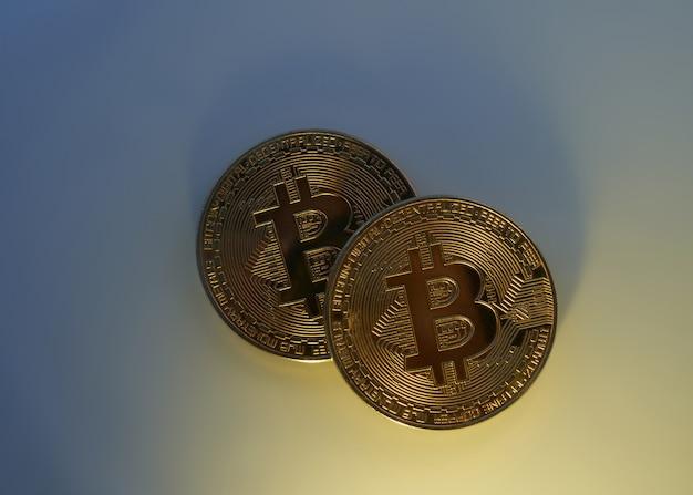 Два золотых биткойна, изолированные на синем фоне крупным планом с копией пространства, концепция роста и падения криптовалюты