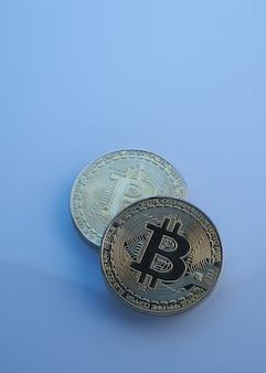 コピースペース、暗号通貨の成長と下降の概念と青い背景のクローズアップで分離された2つの黄金のビットコイン